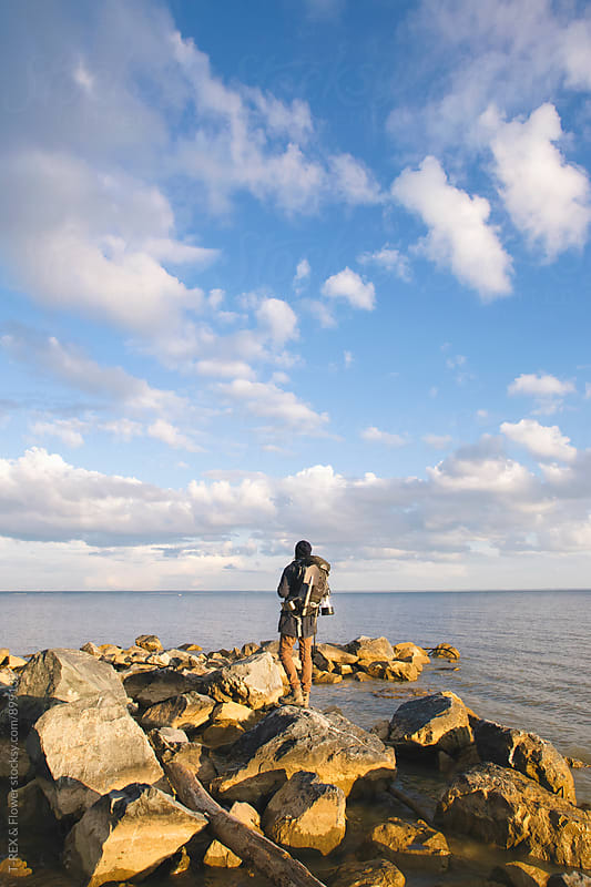 Backpacker looking far away while standing on rocks by Danil Nevsky for Stocksy United