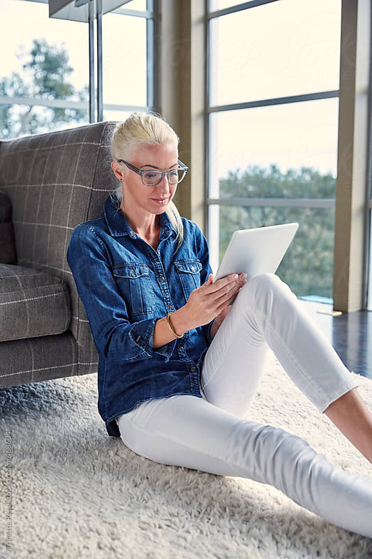 Woman looking at digital tablet in living room by Trinette Reed for Stocksy United