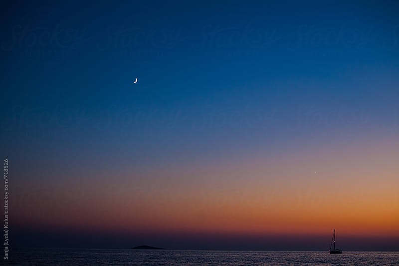 Beautiful sunset on the sea with a boat and a moon in the background by Sanja (Lydia) Kulusic for Stocksy United