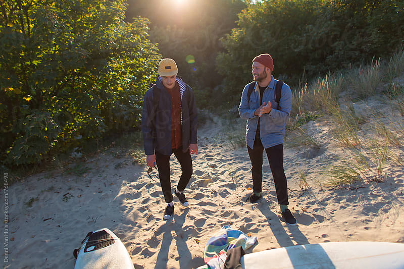 Friends standing in the dunes with their surfboards. by Denni Van Huis for Stocksy United