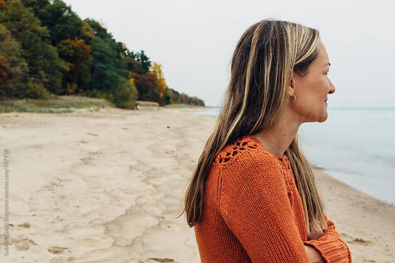 Woman on a lake beach in the fall by Gabriel (Gabi) Bucataru for Stocksy United
