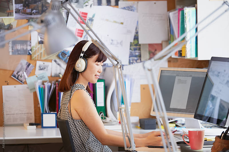 Start up businesswoman working at computer in busy office by Aila Images for Stocksy United