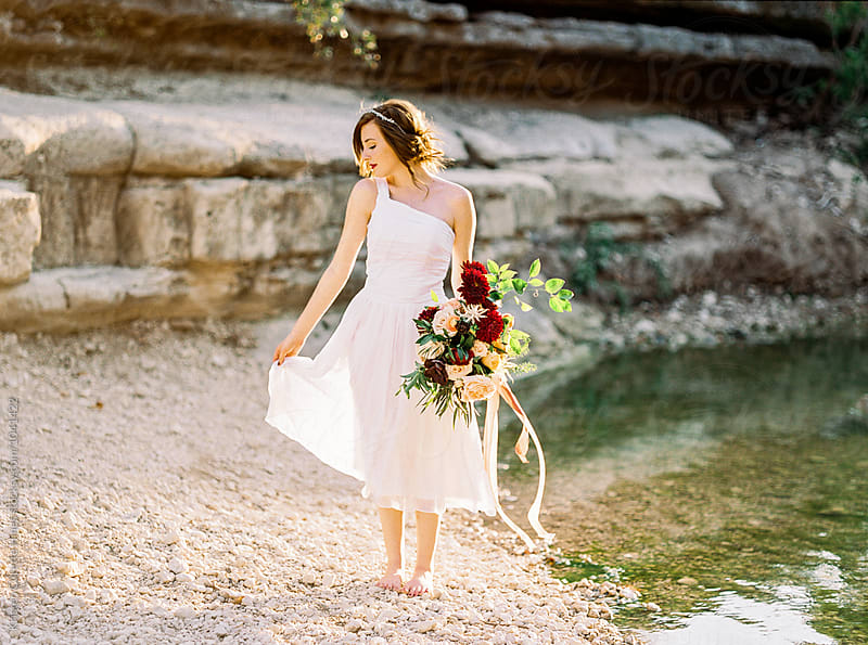 Bridal inspiration / Woman in a white dress standing by water by Kristen Curette Hines for Stocksy United