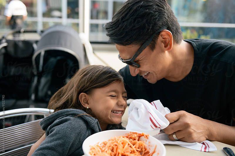 Dad playfully cleans his daughters mouth with a napkin by Emmanuel Hidalgo for Stocksy United