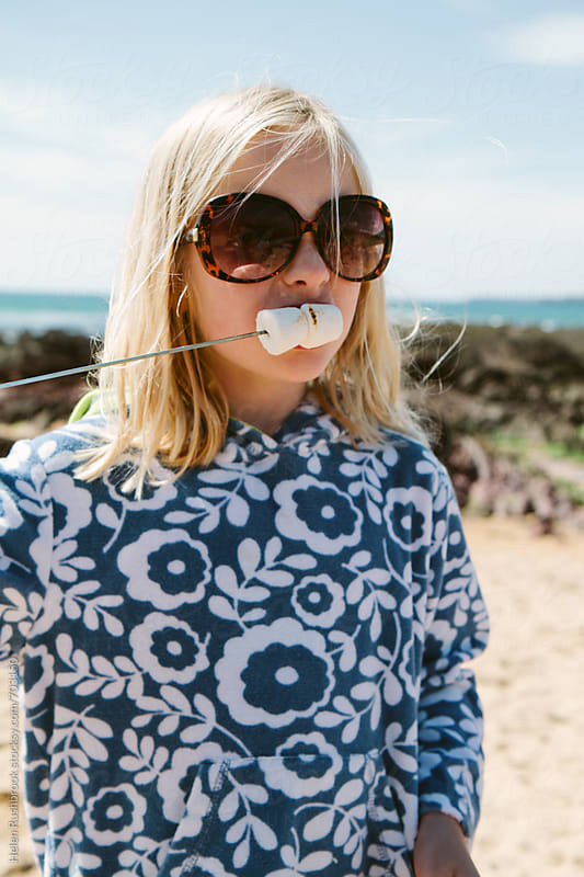 A little girl in shades eating toasted marshmallows on a beach by Helen Rushbrook for Stocksy United