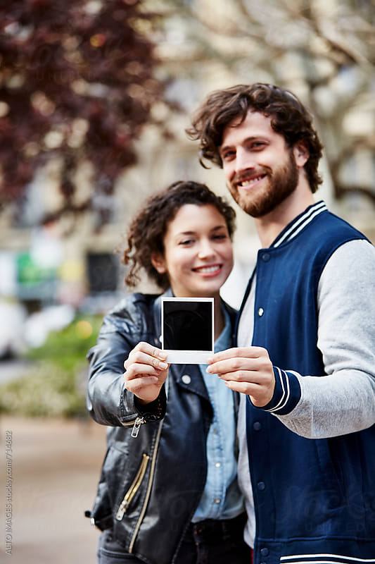 Happy Couple Showing Instant Print In City by ALTO IMAGES for Stocksy United