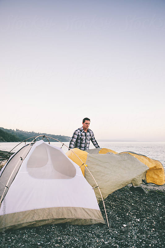 Man setting up a tent on the beach by Suprijono Suharjoto for Stocksy United