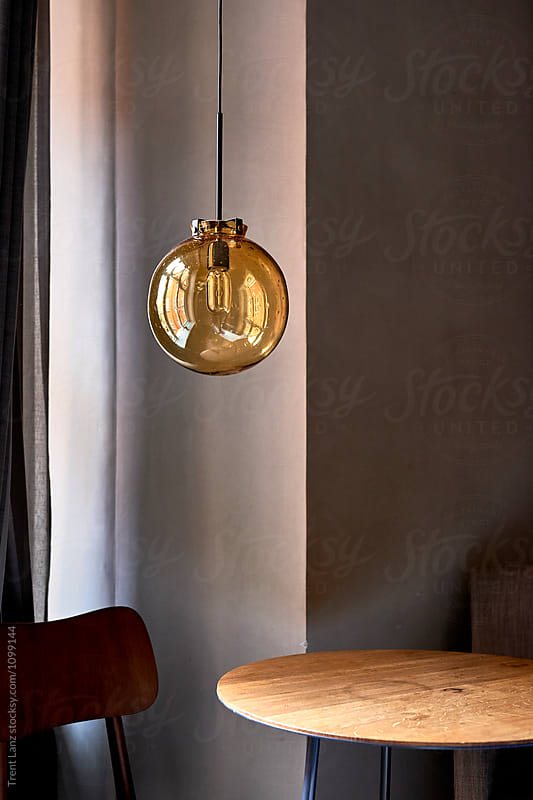 Yellow round ceiling lamp hanging on wire by Trent Lanz for Stocksy United