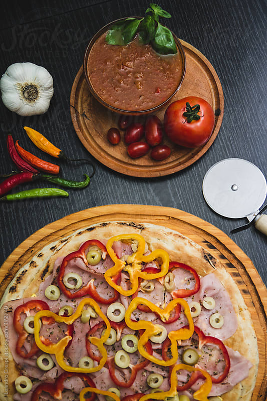 Pizza, red and yellow pepper sliced with ham by Leandro Crespi for Stocksy United