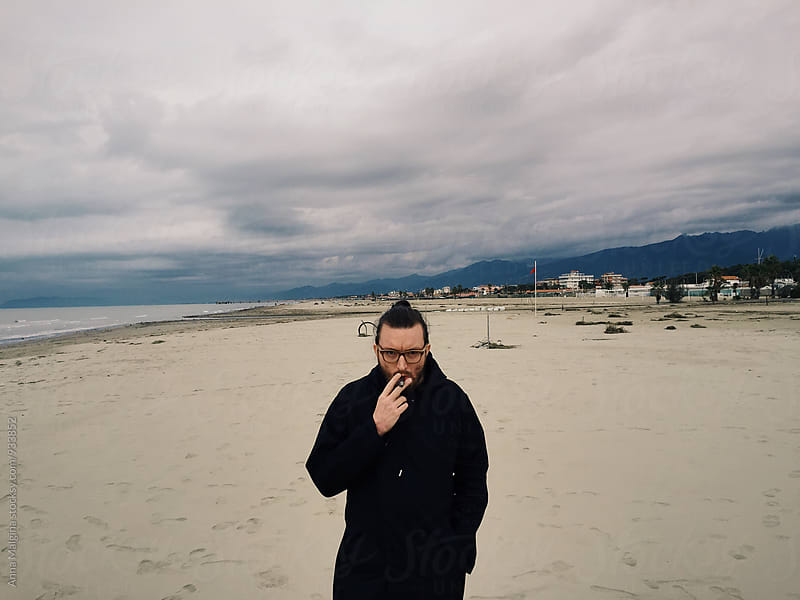 A portrait of a smoking man on the beach by Anna Malgina for Stocksy United