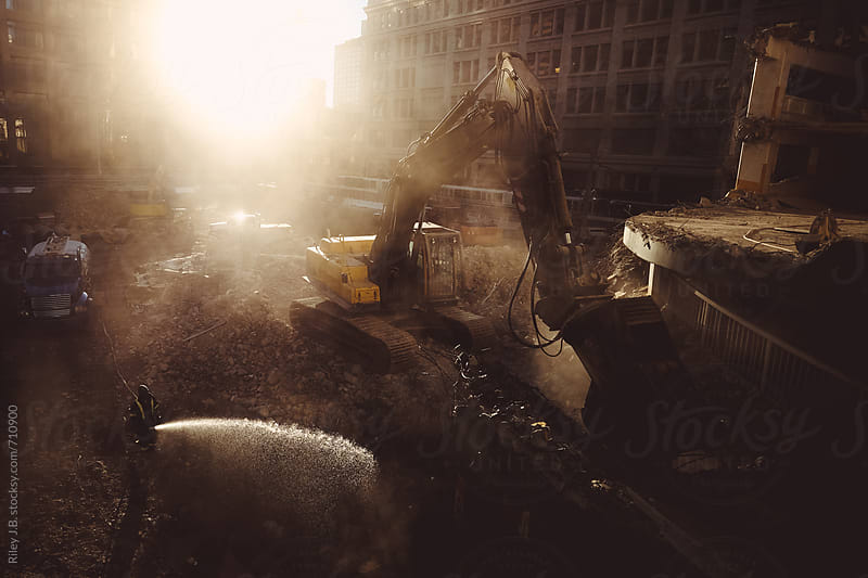 An excavator demolishes a building while a worker sprays water by Riley J.B. for Stocksy United