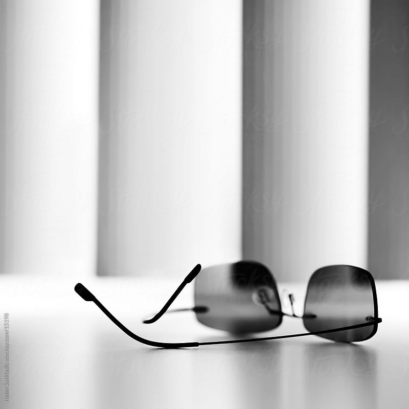 sunglasses on a table in front of window shades by Helen Sotiriadis for Stocksy United