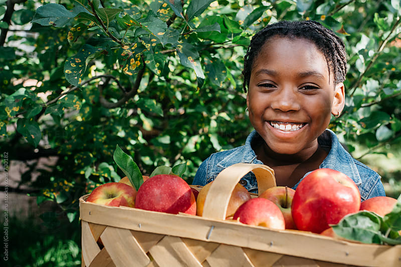Smiling black girl with apples by Gabriel (Gabi) Bucataru for Stocksy United