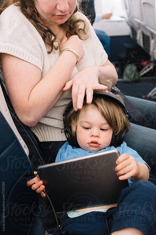 Mother brushes the hair of her son while he watches a show on his tablet. by Lucas Saugen for Stocksy United