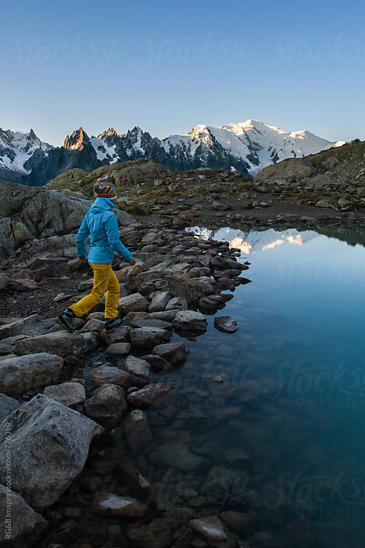 Woman walking along the lake with high mountains in the background by RG&B Images for Stocksy United