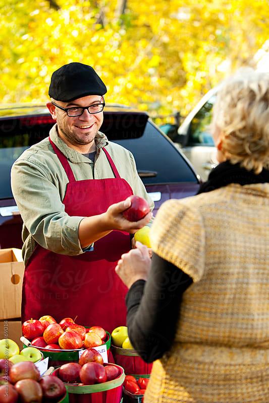 Farmer's Market: Offering Apple to Woman by Sean Locke for Stocksy United