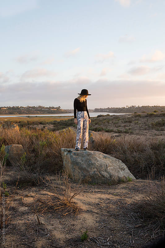 Woman standing on rock in the wilderness by Curtis Kim for Stocksy United