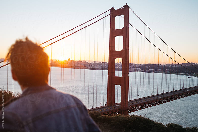 young male in front of golden gate bridge looking away from camera towards city by Jesse Morrow for Stocksy United