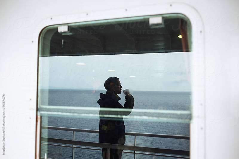 Man smoking cigarette on ferry boat by Marko Milovanović for Stocksy United