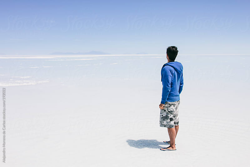 Young man facing back looking to the infinite on Uyuni salt flat landscape. Adventure travel by Alejandro Moreno de Carlos for Stocksy United