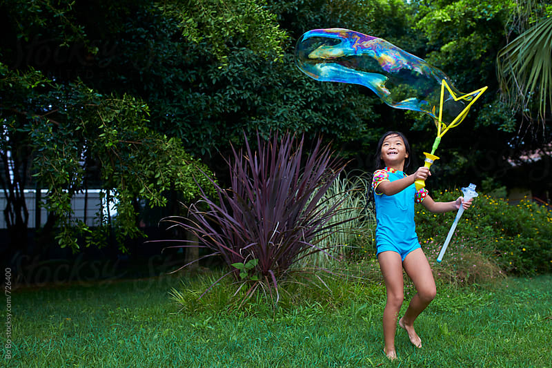 little asian girl playing bubble in the park by Bo Bo for Stocksy United