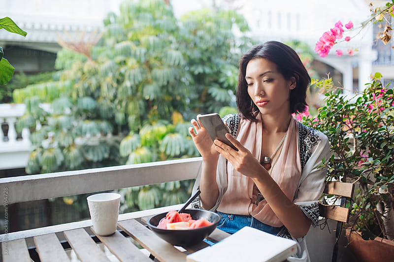 Asian Woman Sitting on the Balcony and Texting by Lumina for Stocksy United