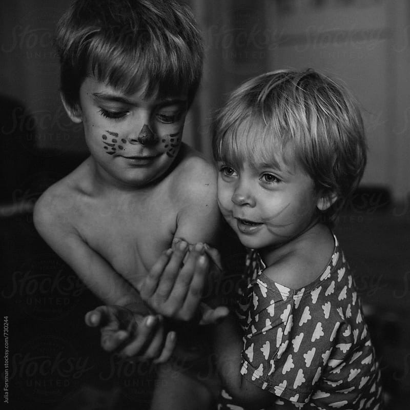 Siblings with painted faces play together. by Julia Forsman for Stocksy United