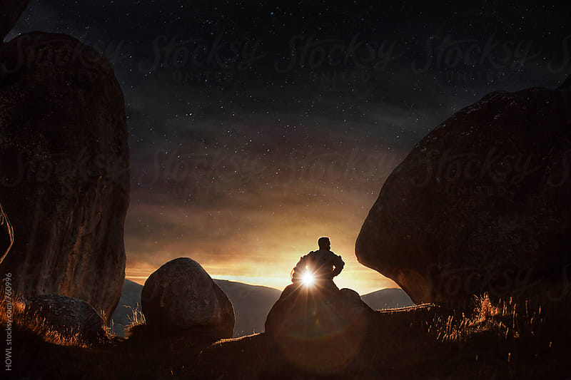 A young astronaut sits and ponders under the setting sun as a starry night emerges above him.  by HOWL for Stocksy United