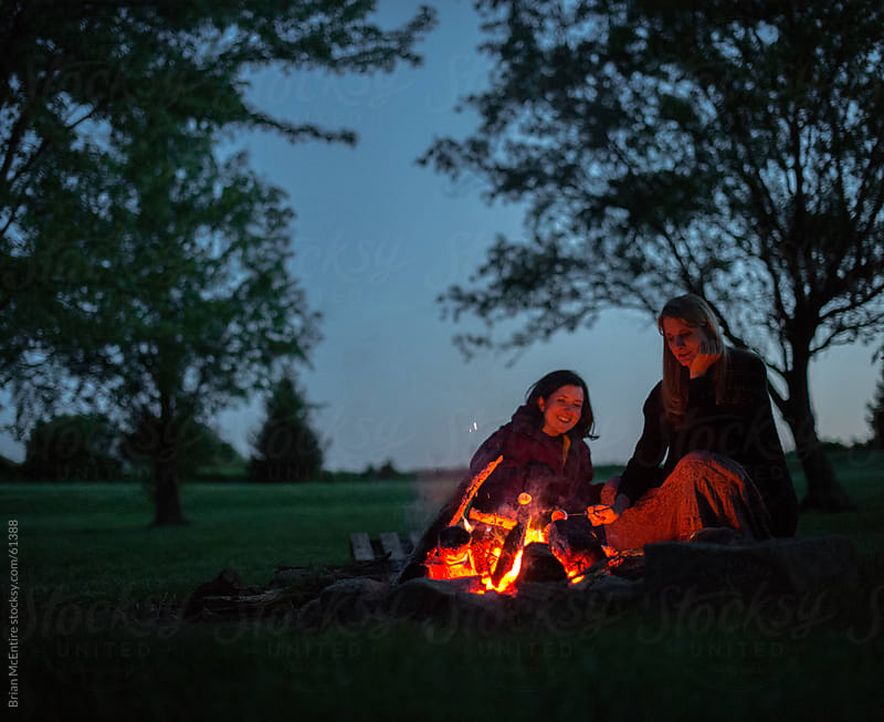 Two women roasting marshmallows by campfire at twilight by Brian McEntire for Stocksy United