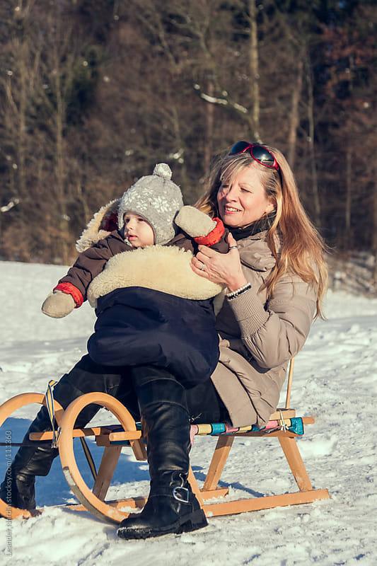 Granny goes sledding with her grandson by Leander Nardin for Stocksy United