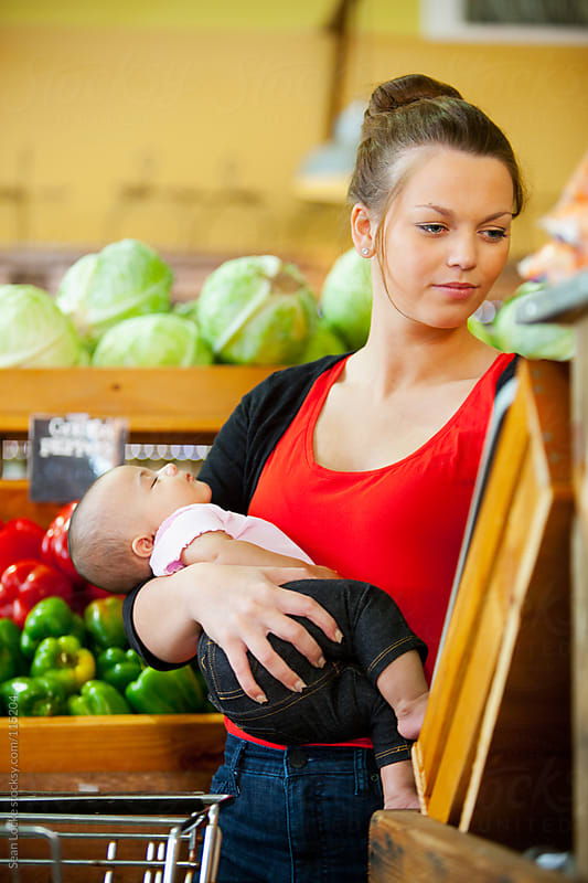 Market: Mother Holds Sleeping Baby While Shopping by Sean Locke for Stocksy United