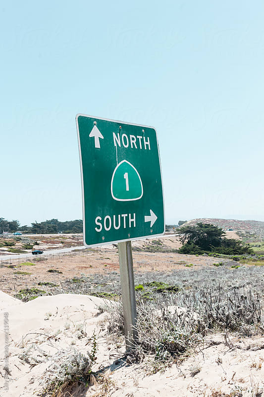 Road sign of Highway 1, pointing north and south by Lilly Bloom for Stocksy United