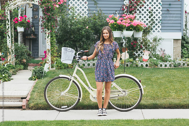 A young girl standing with her bike in front of a pretty floral house by Ania Boniecka for Stocksy United