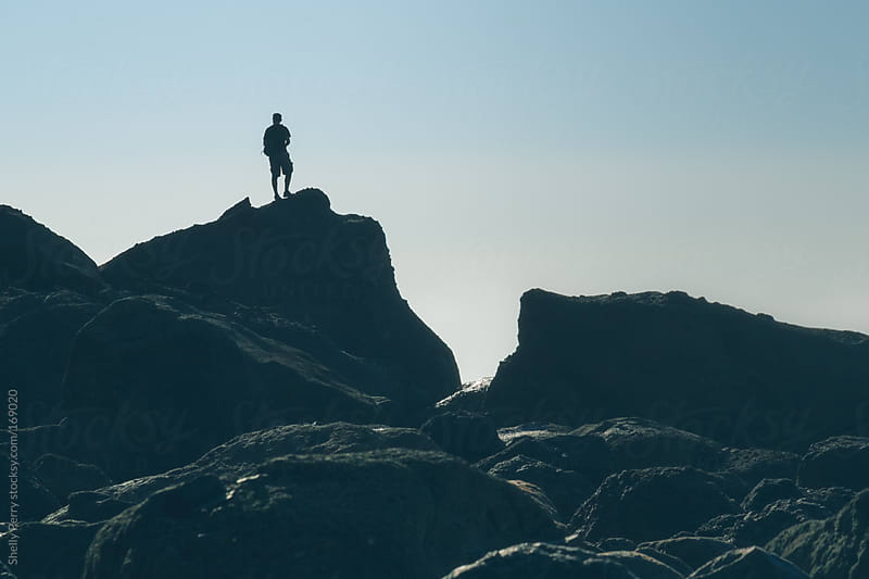 Man stands silhouetted atop large costal boulder by Shelly Perry for Stocksy United
