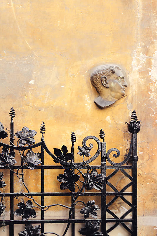 A yellow wall in Rome as the background to a facial profile detail and a cast iron black gate.  by Kaat Zoetekouw for Stocksy United