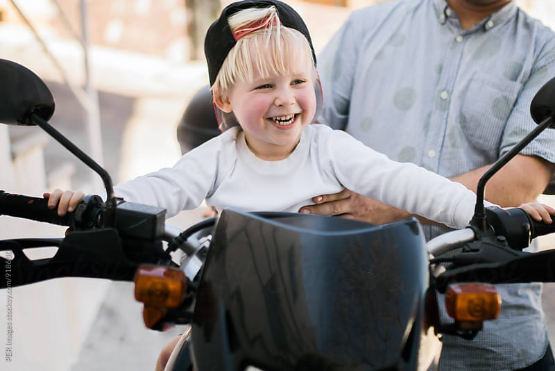 Happy toddler on motorbike by Per Swantesson for Stocksy United