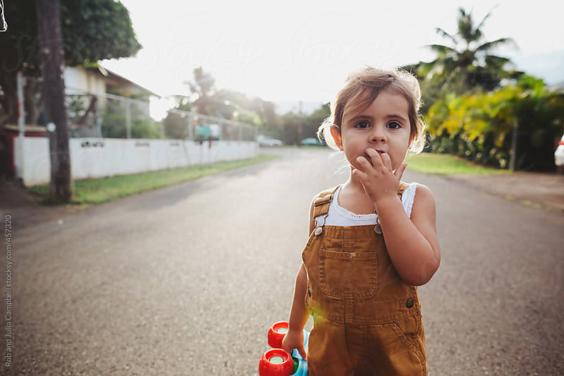 Cute young toddler girl walking on road at sunset by Rob and Julia Campbell for Stocksy United