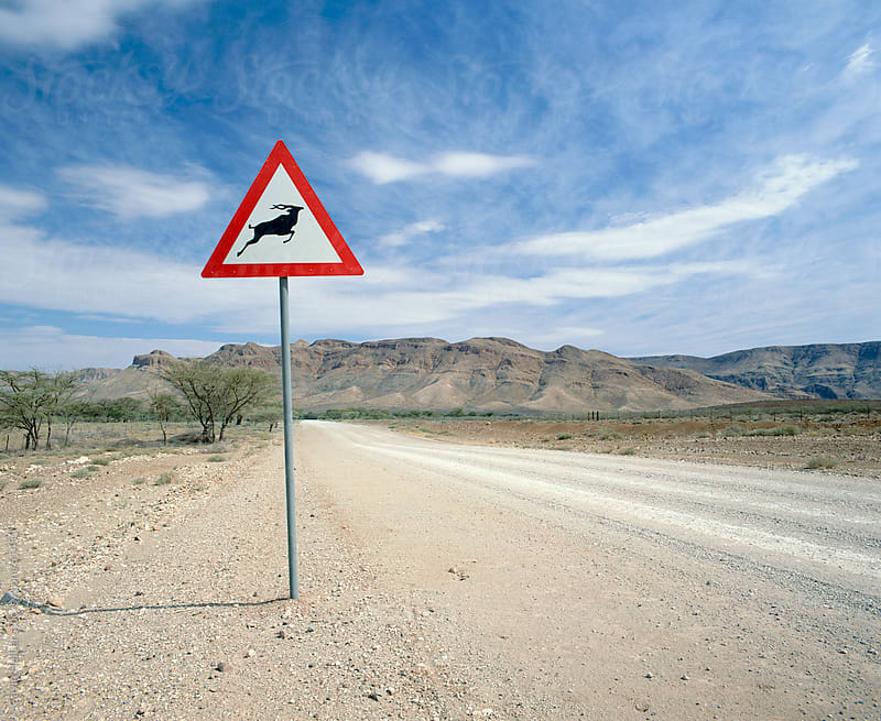 Deer crossing sign along dirt road, Namibia, Africa by Gavin Hellier for Stocksy United