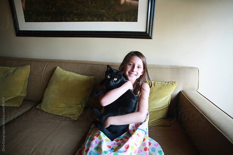 Girl on couch holding a black cat  by Dina Giangregorio for Stocksy United
