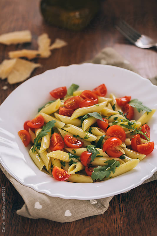 Pasta with fresh tomatoes and rocket salad by Davide Illini for Stocksy United