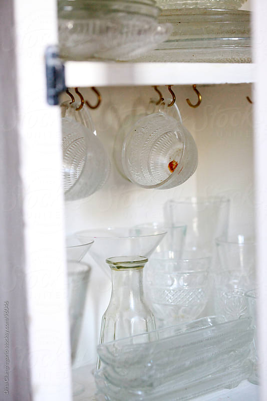 Dirty glass cup hanging in cabinet with other dishes by Dina Giangregorio for Stocksy United