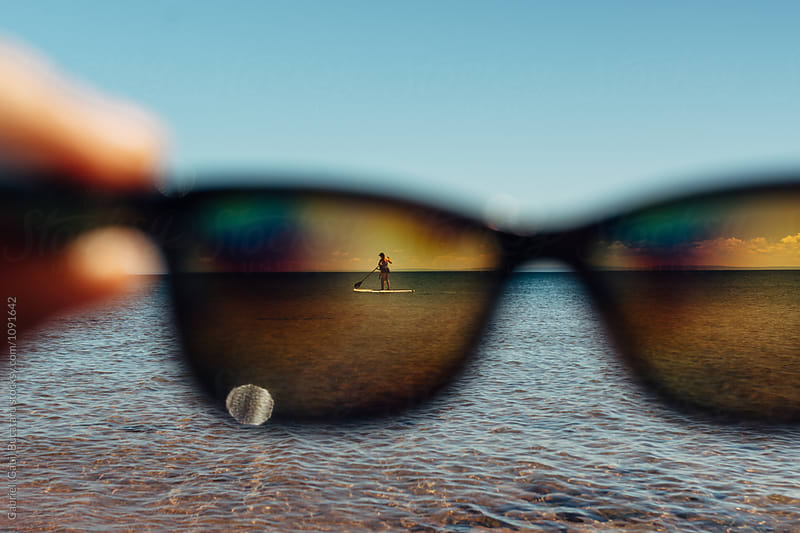Sunglasses framing a mother and daughter paddleboarding by Gabriel (Gabi) Bucataru for Stocksy United
