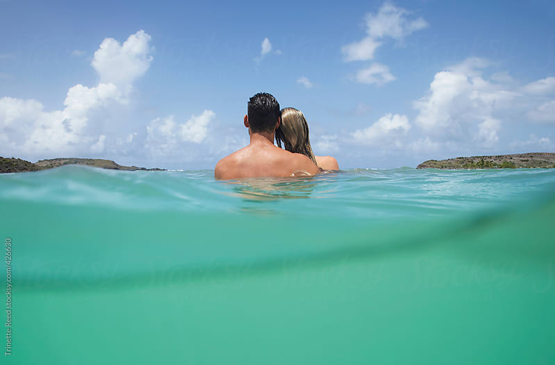 Couple relaxing in the ocean in the Caribbean on vacation  by Trinette Reed for Stocksy United