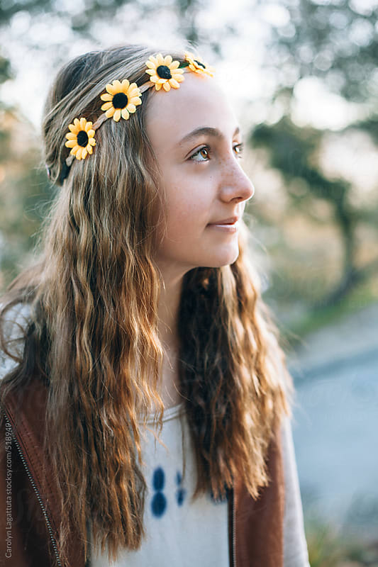 Teenage girl with wavy hair and a sunflower headband by Carolyn Lagattuta for Stocksy United