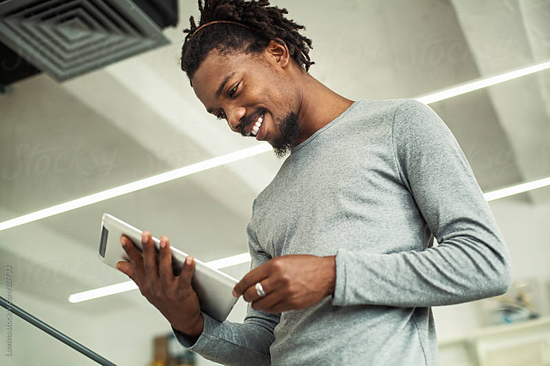 Smiling African Businessman Using a Tablet by Lumina for Stocksy United