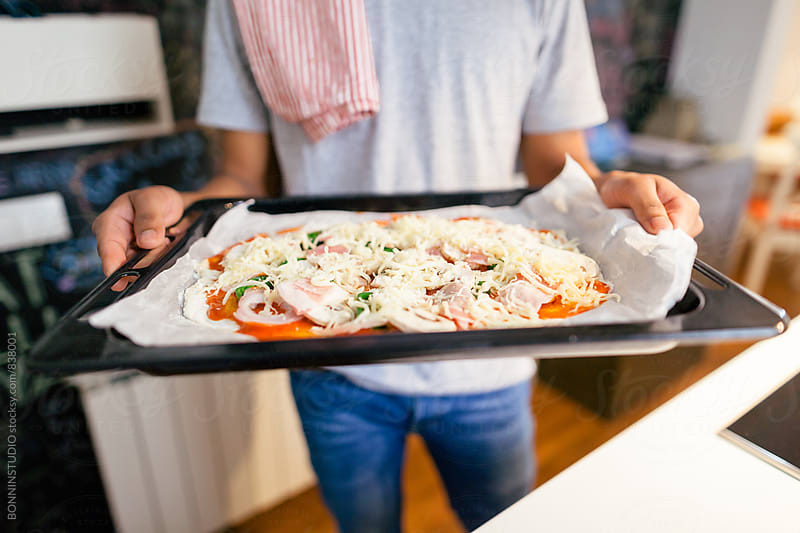 Closeup of a man showing a handmade Italian pizza at home. by BONNINSTUDIO for Stocksy United