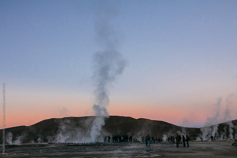 Geyser smoke - steam at sunrise and silhouette of people in Tati by Alejandro Moreno de Carlos for Stocksy United