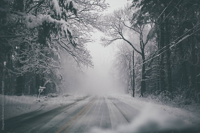 Empty winter road during a snowstorm by Douglas Robichaud for Stocksy United