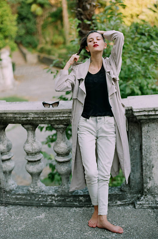 Young brunette posing at old building by Liubov Burakova for Stocksy United