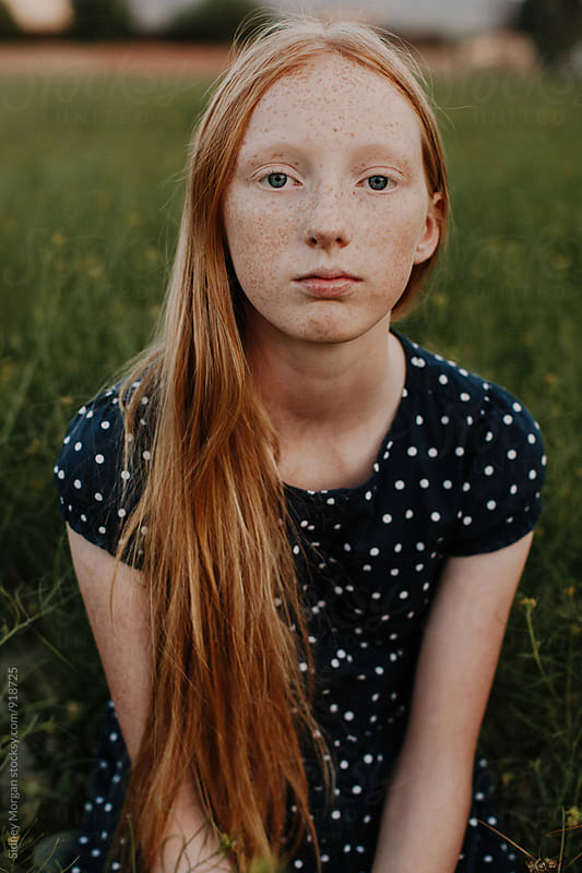 Young Girl Sitting in Field by Sidney Morgan for Stocksy United